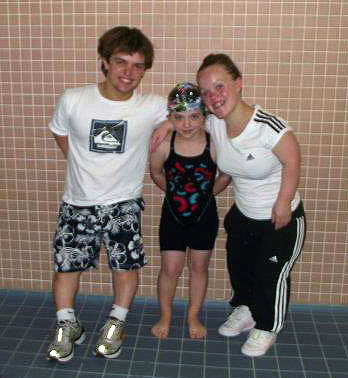 Ellie and Matt with a young swimmer